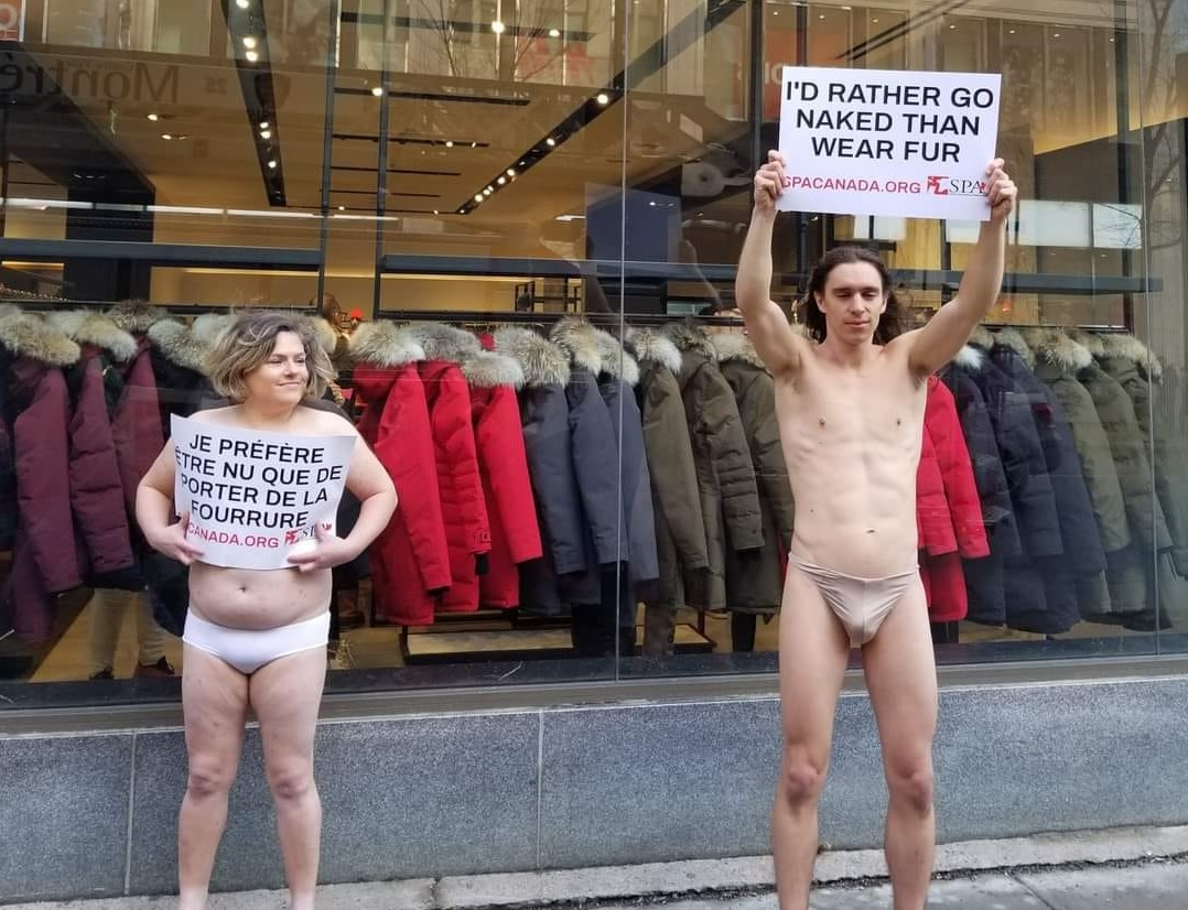 two people are naked and shows poster that i had rather go naked than wear fur